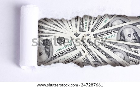 Dollar banknotes through torn white paper - stock photo