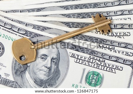 Dollar banknotes with a key close up - stock photo