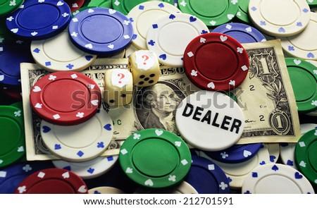 Dollar bill ,casino chips and dice hidden under  question mark- risk concept - stock photo