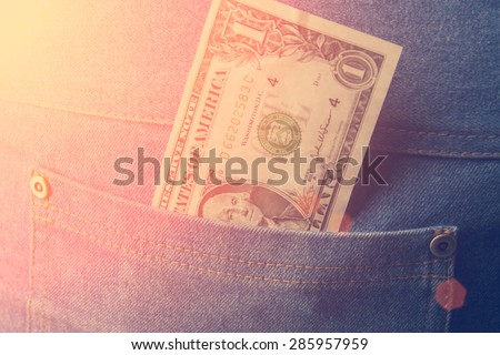 Dollar bill in the back pocket of jeans - stock photo
