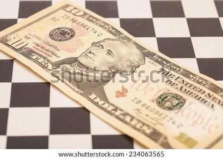 dollar bill on a chess board - stock photo