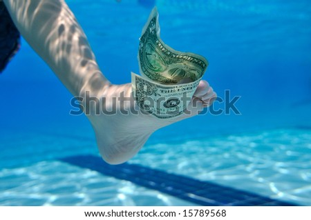 Dollar bill underwater between toes