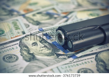 dollar bills and black gun, close up