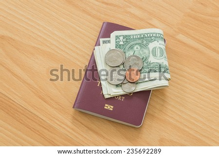 dollar bills and coins thai passport - stock photo