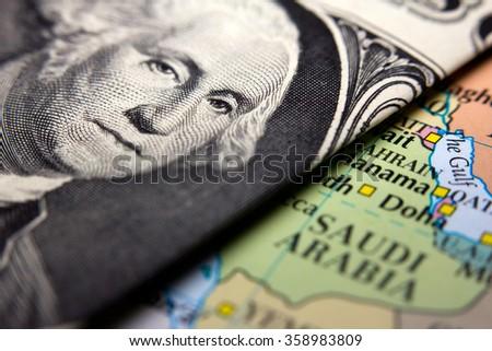 Dollar bills (figuring George Washington) on top of a map of Arabia - stock photo