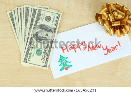 Dollar bills in envelope as gift at New year on wooden table close-up - stock photo