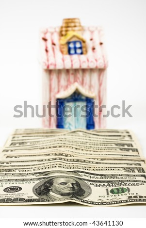 dollar bills leading to a new home on white background - stock photo