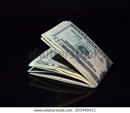 Dollar bills rolled up with clip on black background - stock photo