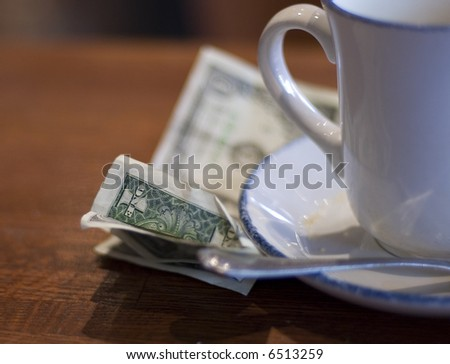 dollar bills under a coffee cup - stock photo