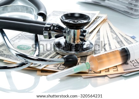 Dollar bills with stethoscope and pills on a white table - stock photo