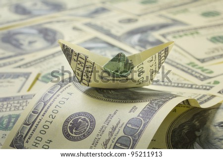 dollar boat swimming in financial sea - stock photo