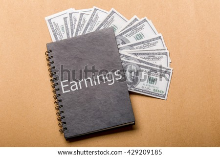 """dollar book and word """"Earnings"""" on cover - stock photo"""