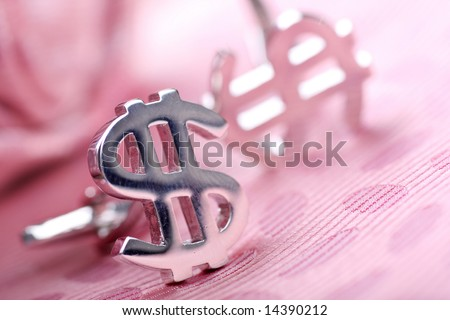 dollar cufflinks discarded with textured tie. Focus on top left of dollar, shallow depth of field for effect - stock photo