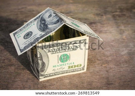 Dollar house on old wood background