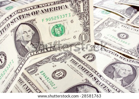 dollar is standing among lying banknotes