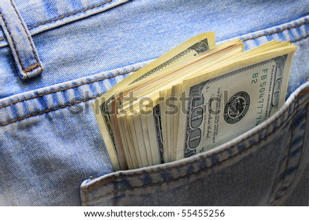 dollar notes in the back pocket of jeans - stock photo