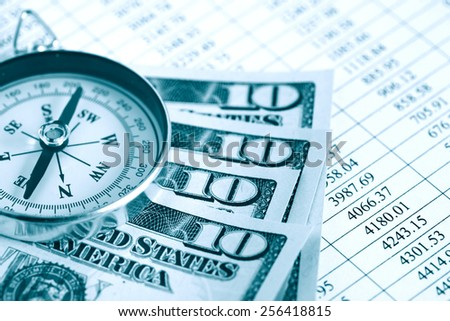 Dollar rate. Closeup of compass and dollar bank notes on paper list with digits - stock photo