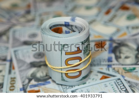 dollar roll on background of many dollars. roll of dollars - stock photo