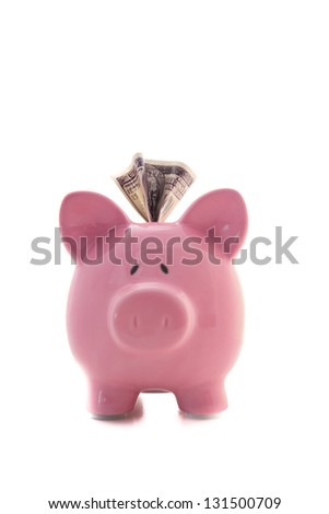 Dollar sticking out of pink piggy bank on white background - stock photo
