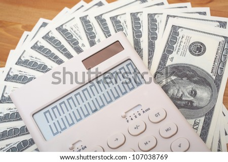 Dollars and calculator close-up - stock photo