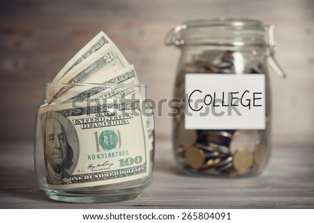 Dollars and coins in glass jar with college label, financial concept. Vintage tone wooden background with dramatic light. - stock photo