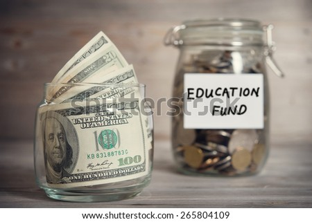 Dollars and coins in glass jar with education fund label, financial concept. Vintage tone wooden background with dramatic light. - stock photo