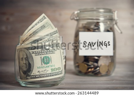 Dollars and coins in glass jar with saving label, financial concept. Vintage tone wooden background with dramatic light. - stock photo
