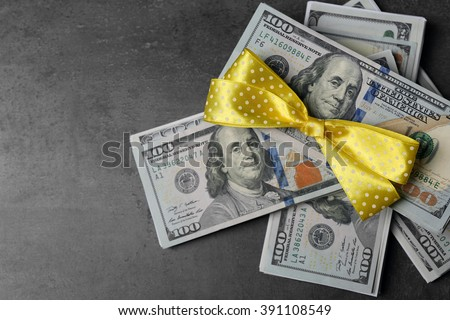 Dollars and colorful bow on grey background