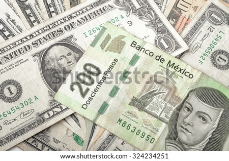 Dollars and Mexican Pesos assorted bills cash pile background - stock photo