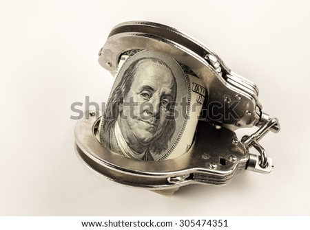 dollars and police handcuffs on a white background - stock photo