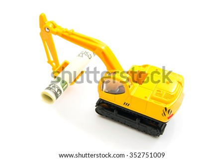 dollars banknotes and yellow backhoe on white closeup