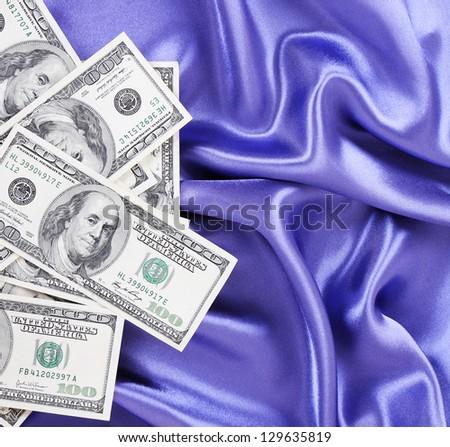 Dollars bills on blue silk fabric, sexy money - stock photo