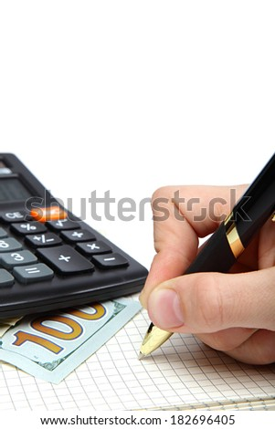 Dollars, calculator and hand with pen on the open notebook. - stock photo