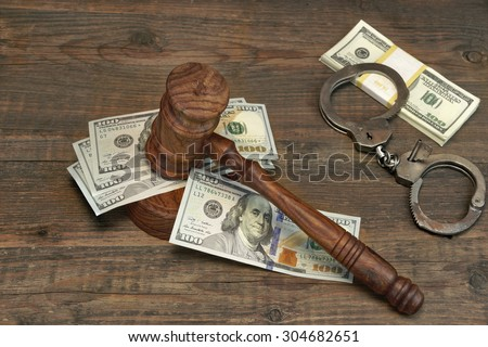 Dollars Cash, Real Handcuffs And Judge Gavel On Rough Wood Background. Concept For Arrest, Corruption, Bail, Crime, Bribing or Fraud. - stock photo