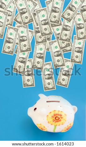 Dollars coming into piggy bank (moneybox). - stock photo