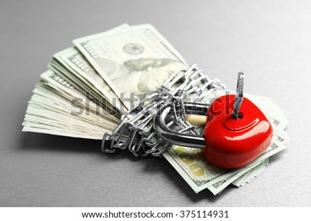 Dollars currency with lock and chain on gray  background - stock photo