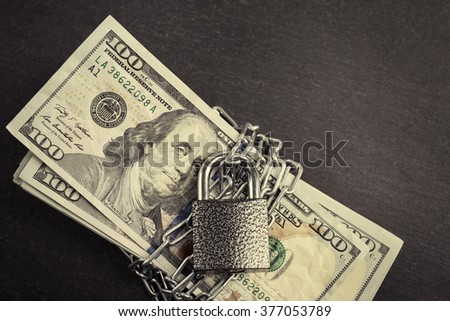 Dollars currency with lock and chain on grey background - stock photo
