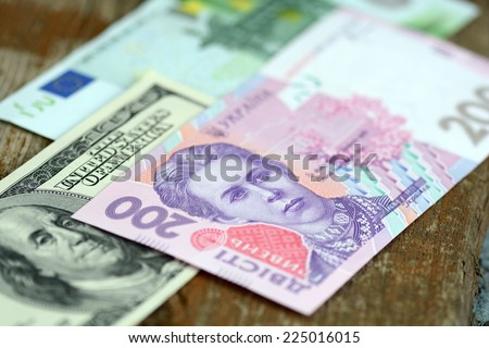 dollars euro and hryvnia banknotes on wooden background - stock photo