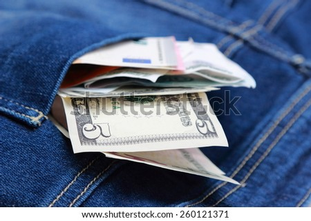 Dollars, euro and russian rubles in jeans pocket