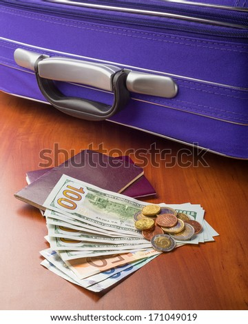 Dollars, Euros and Passports with a violet suitcase, ready for a business or holiday travel abroad. - stock photo
