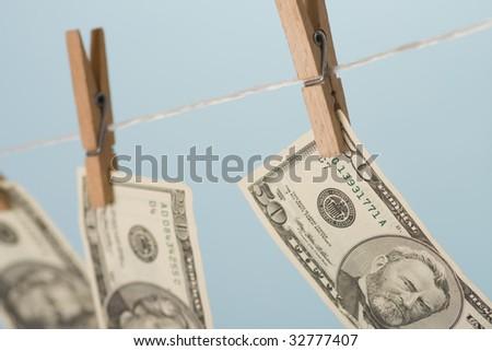 dollars hanging on line on blue background - stock photo