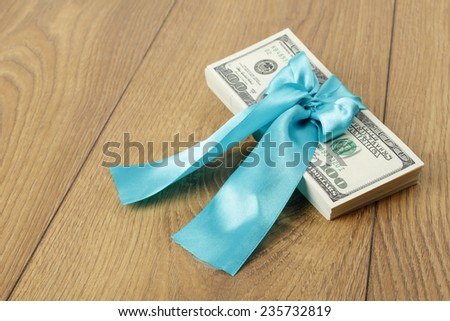 Dollars in a blue ribbon on wooden background on Holiday - stock photo