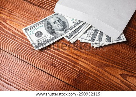 Dollars in an envelope lying on wooden table with place for text