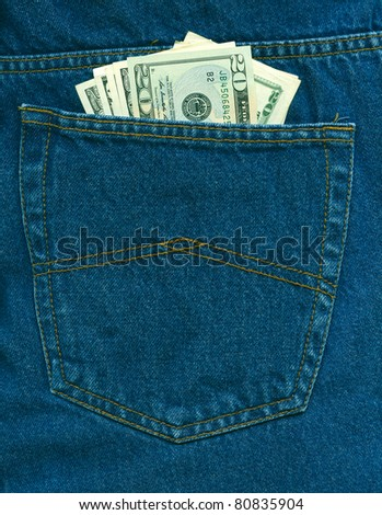 Dollars in dark blue jeans back pocket - stock photo