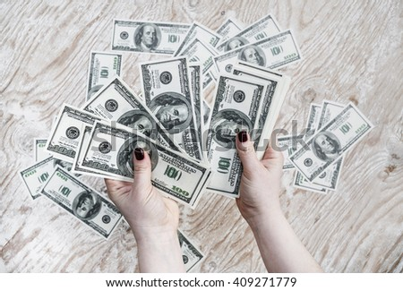 Dollars in hands. Cash in hands. Fake money in hands. Money in female hands on light wooden background. - stock photo
