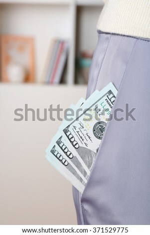 Dollars in pocket of gray pants on unfocused background closeup
