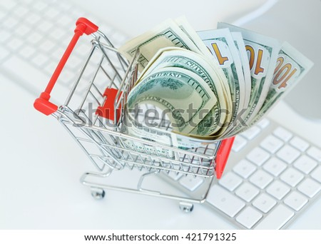 Dollars in the shopping cart on a computer keyboard - concept of online shopping - stock photo