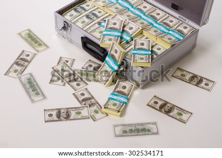 Dollars scattered with suitcases. Suitcase full of money. - stock photo