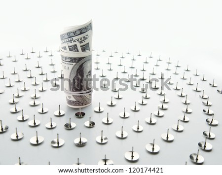 Dollars surrounded by thumbtacks being impossible to reach - stock photo