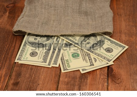 dollars with burlap sack on wooden background